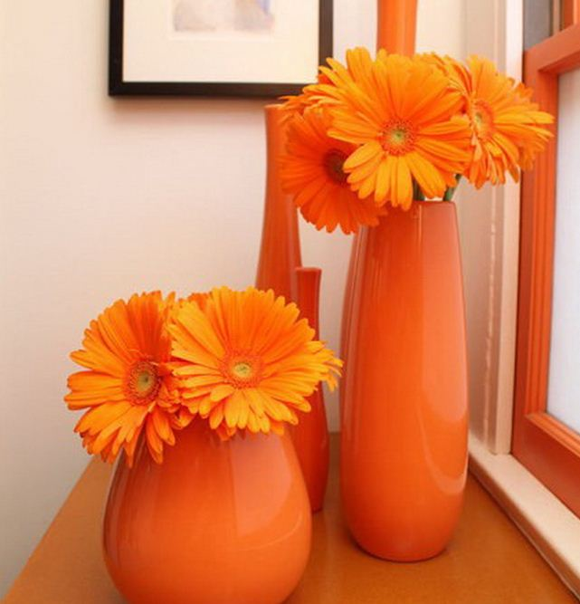 Яркие вазы апельсинового оттенка с оранжевыми цветами выступают в качестве сильного цветового акцента