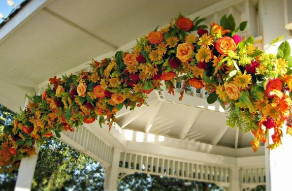 Объемные гирлянды из искусственных цветов используют в торжественном оформлении