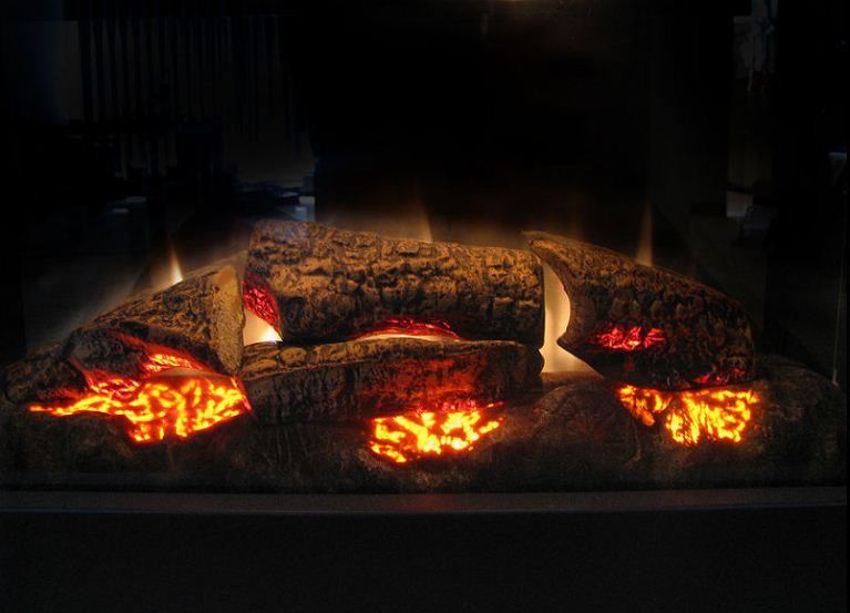 Электрический камин лишь производит визуальное впечатление горящего пламени и тлеющих дров.