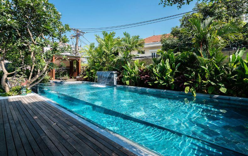 Плавательный бассейн в окружении экзотических растений.