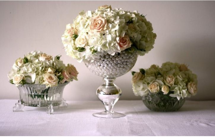 Композиции из цветков двух пастельных оттенков в хрустальных низких вазах.