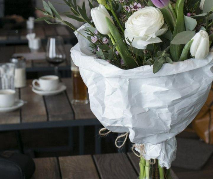 Букет в бумажной упаковке в простой стеклянной вазе или банке