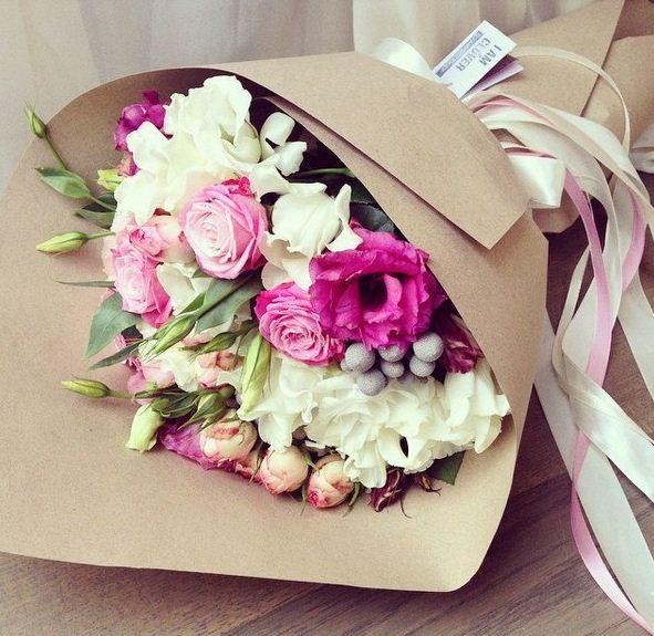 Букет цветов, упакованный в бумагу и украшенный лентами.