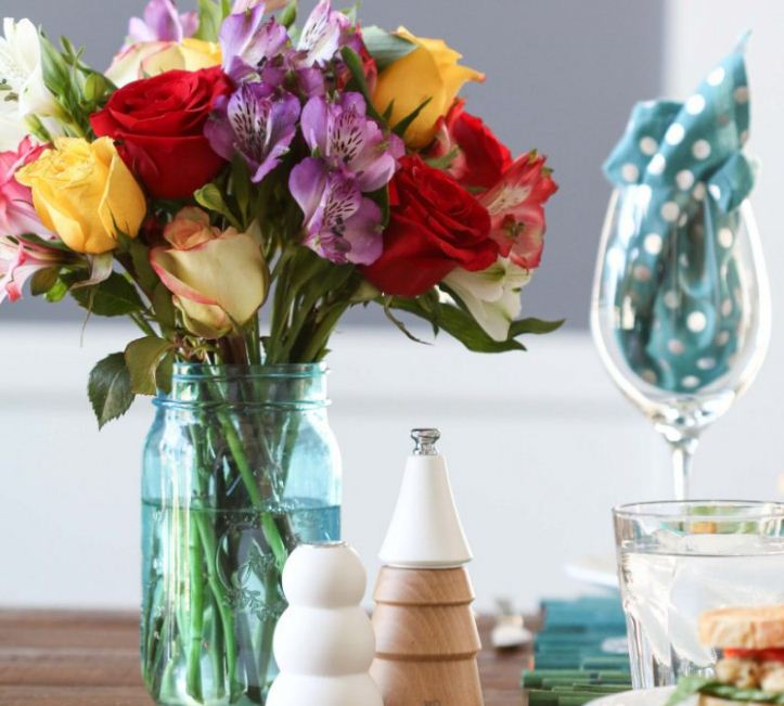 Букет из ярких цветов в простой стеклянной банке.