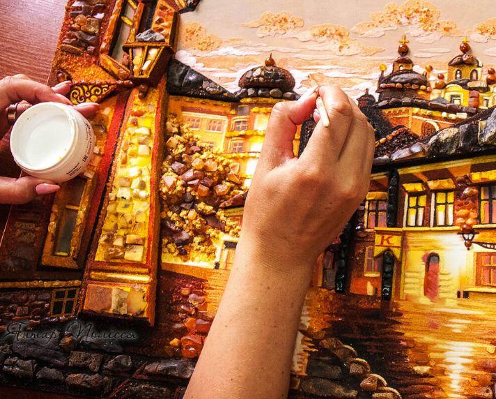 Мастер наносит клей и прикрепляет кусочек янтаря