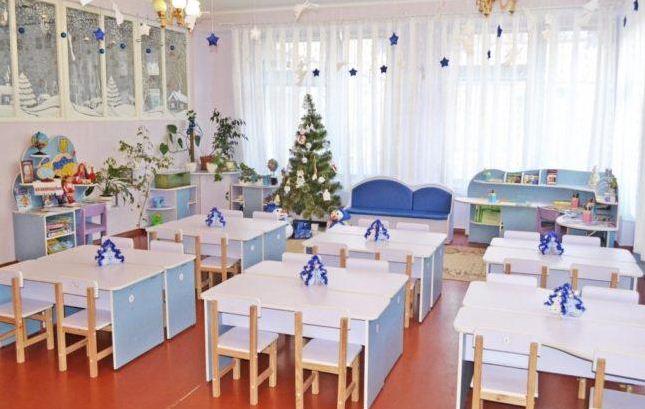 Стилизованные фигурки новогодних елочек на столах дополняют праздничное оформление группы