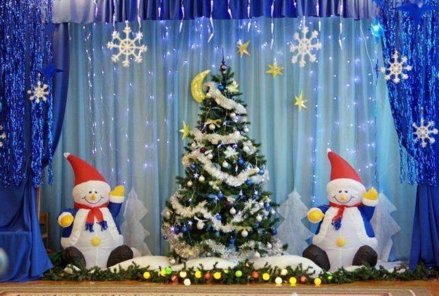 Объемные фигурки снеговиков и елка на фоне центральной стены музыкального зала