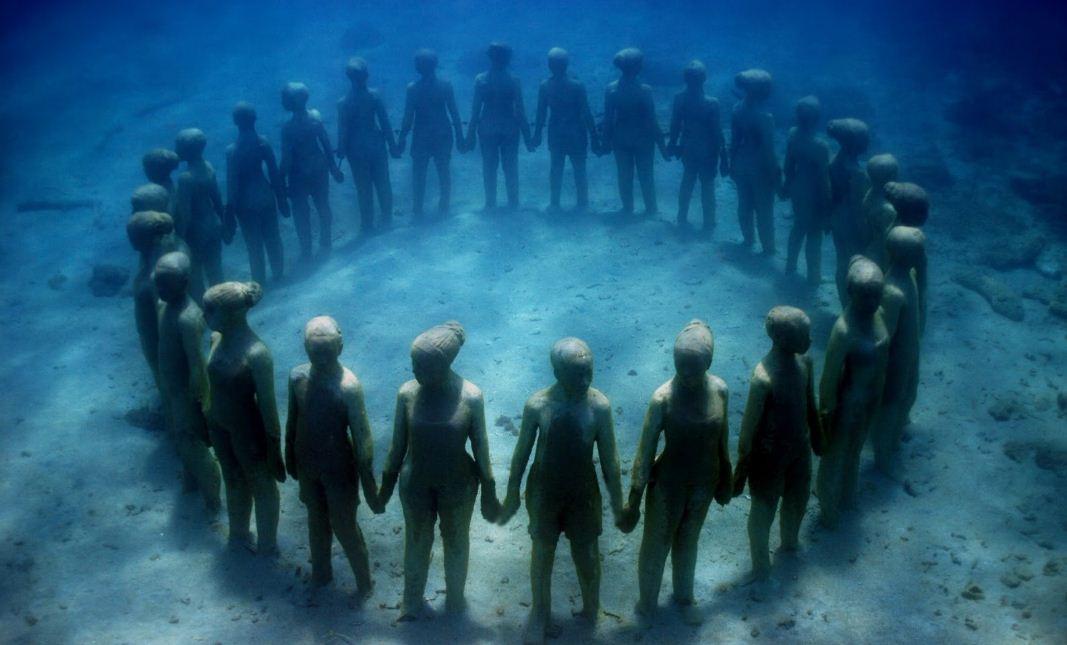 Подводные статуи стоят в кругу, взявшись за руки.